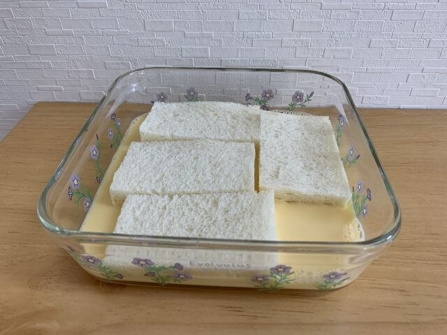 耐熱皿に入った卵液と食パンの写真